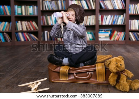 Playful childhood. Little boy having fun at room with bookshelf and sitting at suitcase. Boy pretending to be pilot - stock photo
