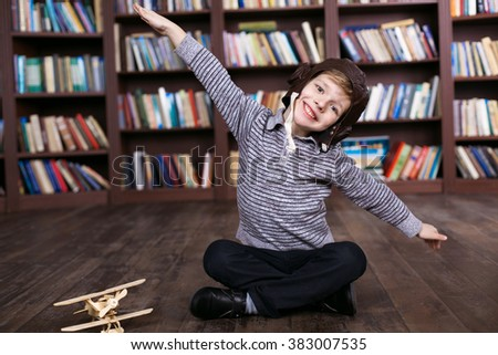 Playful childhood. Little boy having fun at room with bookshelf. Boy pretending to be pilot - stock photo