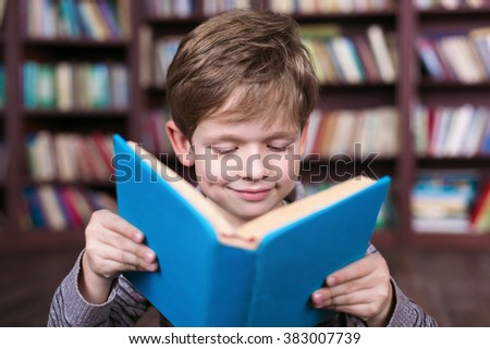 Playful childhood. Little boy having fun at room with bookshelf. Boy reading book - stock photo