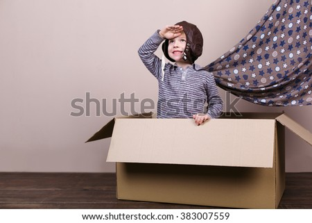 Playful childhood. Little boy having fun with cardboard box. Boy pretending to be pilot - stock photo