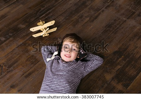 Playful childhood. Little boy having fun with plane. Boy pretending to be pilot. Boy playing at room on wooden floor - stock photo
