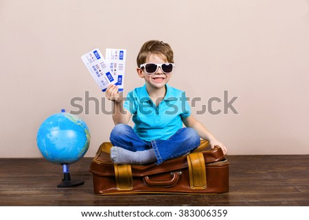 Playful childhood. Little boy with sunglasses going on trip. Boy sitting at suitcase near globe and holding tickets - stock photo