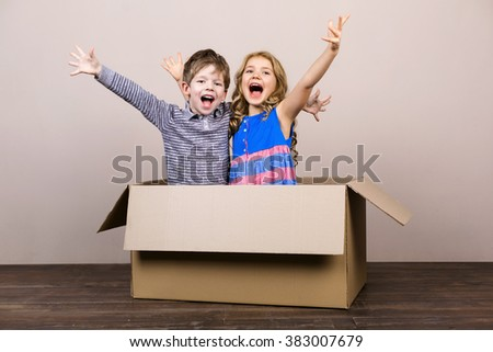 Playful childhood. Little children having fun with cardboard box. Children cheerfully smiling - stock photo