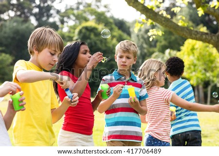 Playful children blowing bubbles wand in the park - stock photo