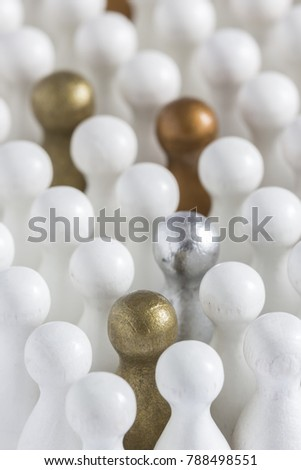 Playful Concepts: Gold, Silver and Bronze game pieces in a crowd of white pieces