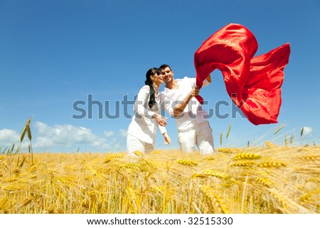 Playful confident couple of mid adult man and woman standing in yellow corn field together embracing in casual clothes and throwing a red big scarf - stock photo