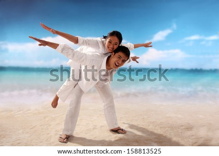 Playful couple at the beach - stock photo