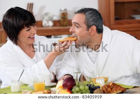 Playful couple having breakfast - stock photo