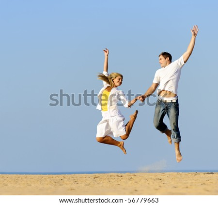 Playful couple jumping and smiling on the beach - stock photo