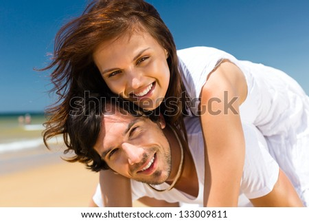 Playful couple on the ocean beach enjoying their summer vacation, the man is carrying the woman piggyback - stock photo