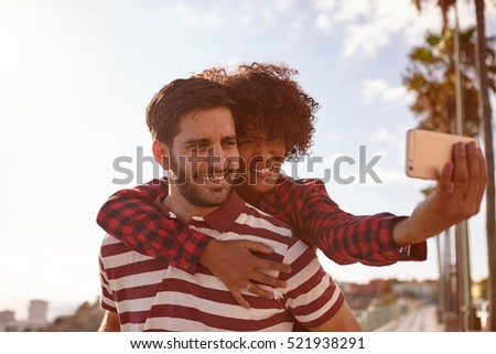 Playful couple taking selfies with toothy smiles while she sits on his back and he holds her up with both his hands