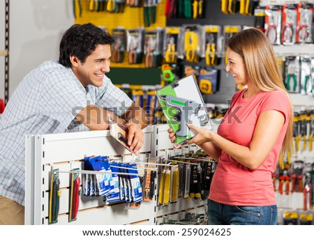 Playful couple with cordless drill in hardware store - stock photo