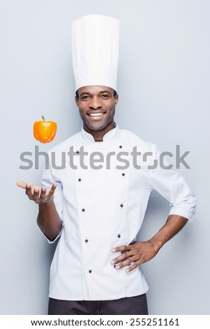 Playful culinary master. Confident young African chef in white uniform throwing pepper and looking at camera with smile while standing against grey background - stock photo