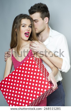 Playful cute young couple standing close to each other, embraces, holding big spotted red present box, vertical photo - stock photo