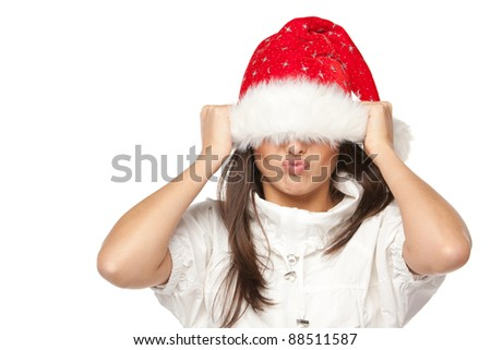 Playful cute young woman in Santa hat having fun pulling down the hat over the eyes on white background. - stock photo