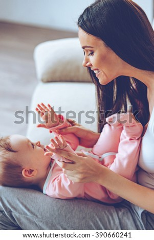 Playful cutie. Side view of cheerful beautiful young woman holding baby girl on her knees and looking at her with love while sitting on the couch at home - stock photo