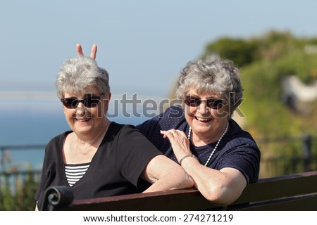 Playful elderly twin sisters by the ocean - stock photo