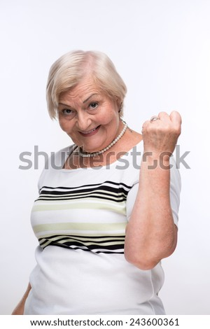 Playful elderly woman. Closeup portrait of smiling elderly woman showing her fist up while standing against white background - stock photo