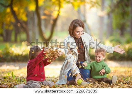 Playful family enjoying autumn day in a park - stock photo