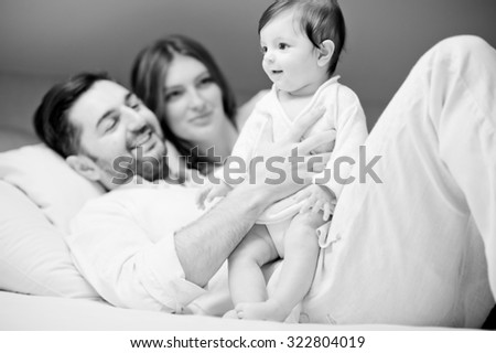 Playful family on white bed in white bedroom, lightly noised black and white portrait - stock photo