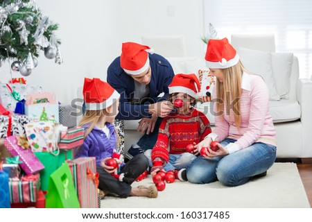 Playful family with Christmas gifts and ornaments sitting at home