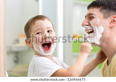 playful father and his kid son shaving and having fun in bathroom - stock photo
