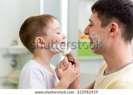 playful father and his son shaving and having fun in bathroom - stock photo