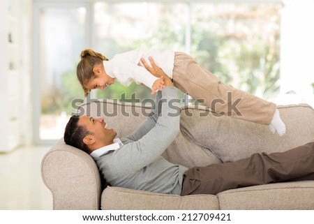 playful father lying on the couch and lifting up his cheerful daughter at home - stock photo