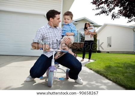 Playful father sitting on tricycle with son while wife standing in background with daughter