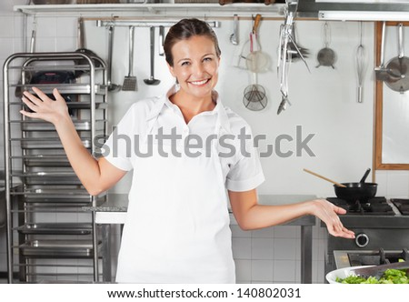 Playful female chef gesturing in commercial kitchen - stock photo