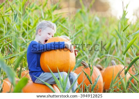 playful funny boy being silly and enjoying pumpkin patch - stock photo