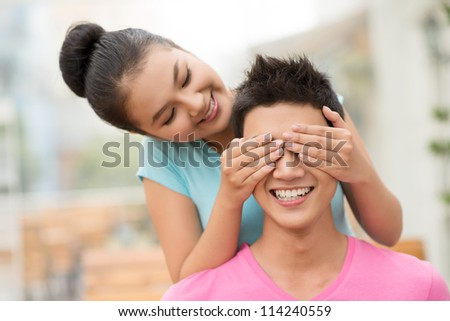 Playful girl covering the guy�¢??s eyes for him to guess who is behind - stock photo