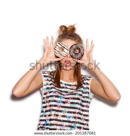Playful girl holding donuts on her eyes. Woman showing own. White background, not isolated - stock photo