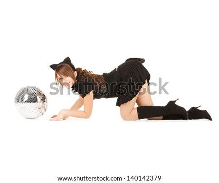 playful girl in cat costume sneaking up to glitter ball - stock photo