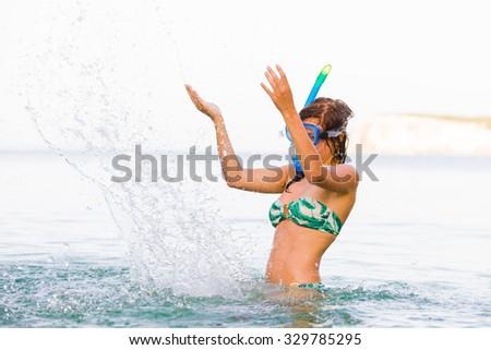 Playful girl splashing the salty seawater of the Mediterranean sea. - stock photo