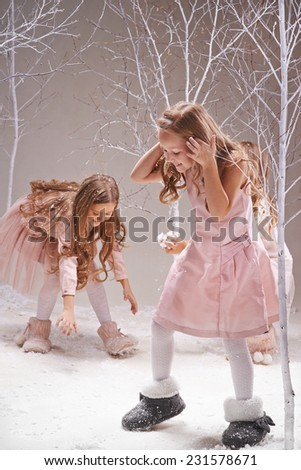 Playful girls in smart dresses playing snowballs in winter forest - stock photo