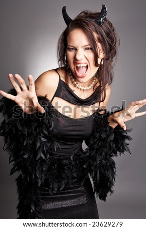 Playful good lucking adult woman dressed as a witch. - stock photo