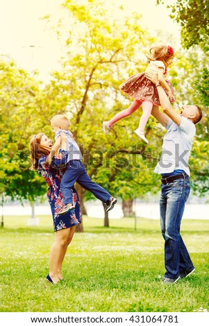 Playful happy family in the park - stock photo