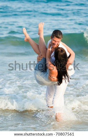 Playful Happy positive expressing couple of men and women smiling walking down the coast beach - stock photo