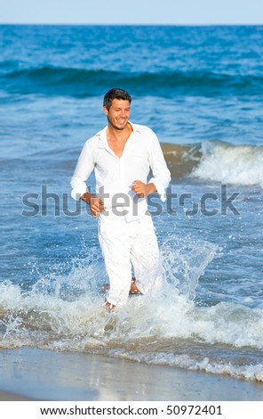 Playful Happy positive expressing man of  smiling walking down the coast beach