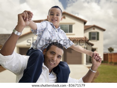 Playful Hispanic Father and Son in Front of Beautiful House. - stock photo