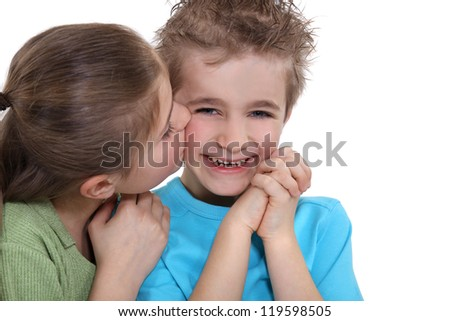 Playful little boy being kissed by a little girl - stock photo