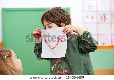 Playful little boy holding paper with smile drawn on it while looking at girl in art class - stock photo