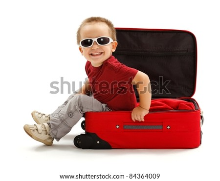 Playful little boy wearing sunglasses, sitting in red suitcase