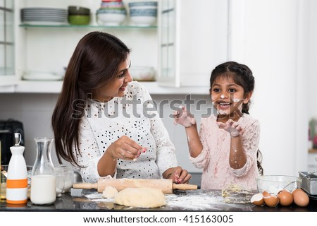 Playful little girl cooking with her mother - stock photo