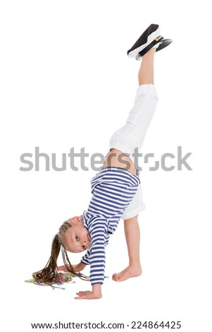 Playful little girl dressed as a sailor boy performs gymnastic exercise. Girl is six years - stock photo