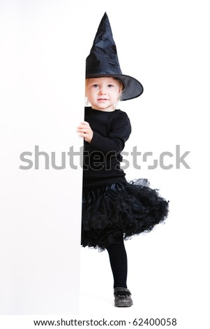 Playful little girl dresses for Halloween in witch costume hiding behind white banner - stock photo