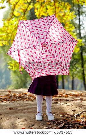 Playful little girl hiding behind colorful umbrella outdoors - stock photo