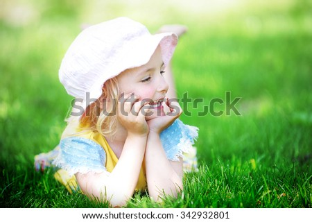 playful little girl in hat on grass. may day - stock photo