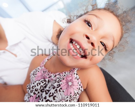 Playful little girl laughing at camera - stock photo